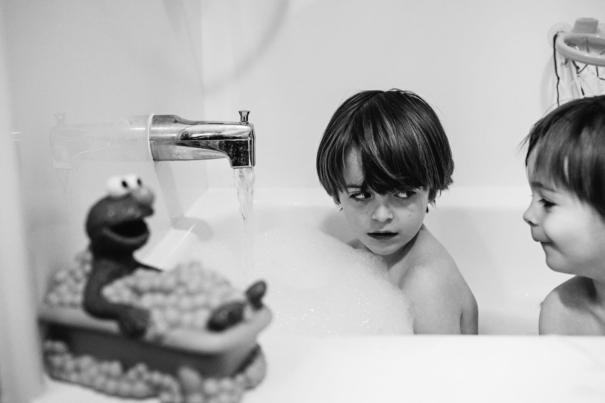 Brother in bathtub giving his sibling a dirty look