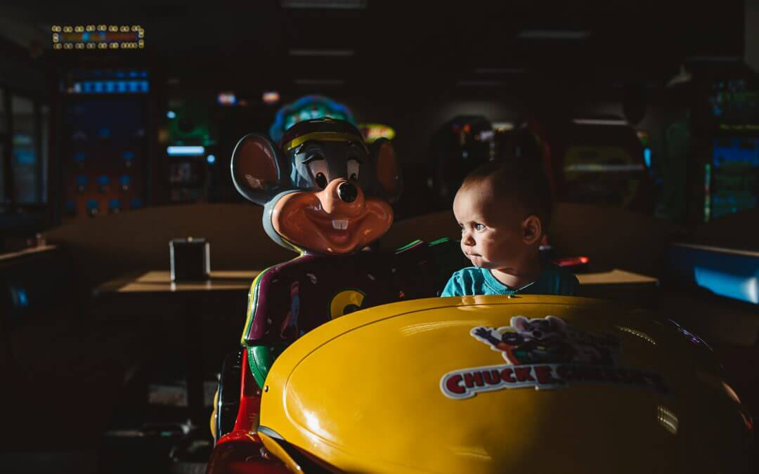 Toddler On Ride at Chuck E. Cheese with dramatic lighting