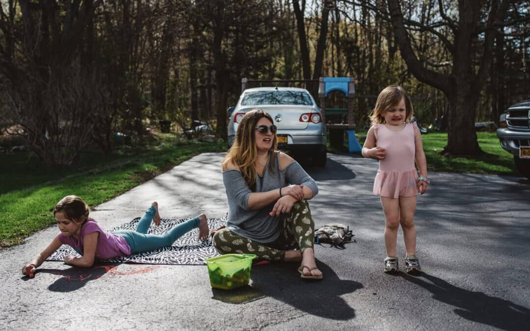Mom looking off into the distance while one of her children draws with chalk in the driveway and the other one is having a tantrum